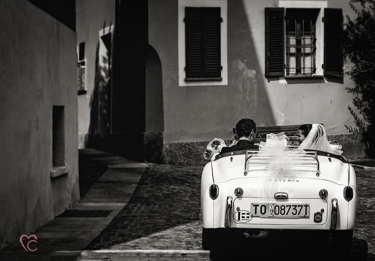 Fotografo matrimonio Torino, matrimonio a peccato Torinese,sposa norvegese, sposi si allontanano su decappottabile bianca d'epoca, bianco e nero