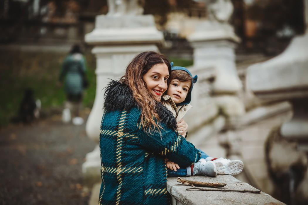 Fotografia di famiglia in autunno nel parco del Valentino a Torino mamma con bambino sulla fontana dei mesi
