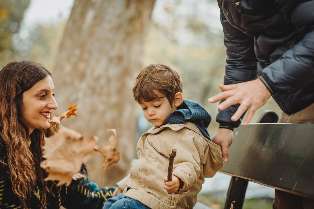 fotografia di famiglia in autunno nel parco del Valentino, bambino che gioca con le foglie secche lanciate dal papà