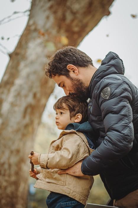fotografia di famiglia in autunno nel parco del Valentino, papà che bacia il bambino sulla testa
