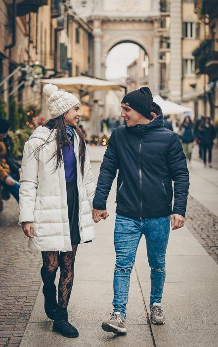Sessione fotografica di coppia natalizia. Coppia che passeggia per la via centrale di Chieri tenendosi per mano