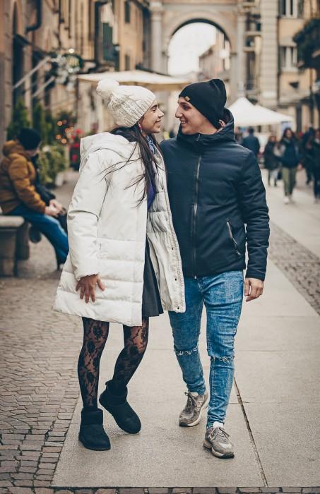 Sessione fotografica di coppia natalizia. Coppia che passeggia per la via centrale di Chieri tenendosi per mano e guardandosi negli occhi