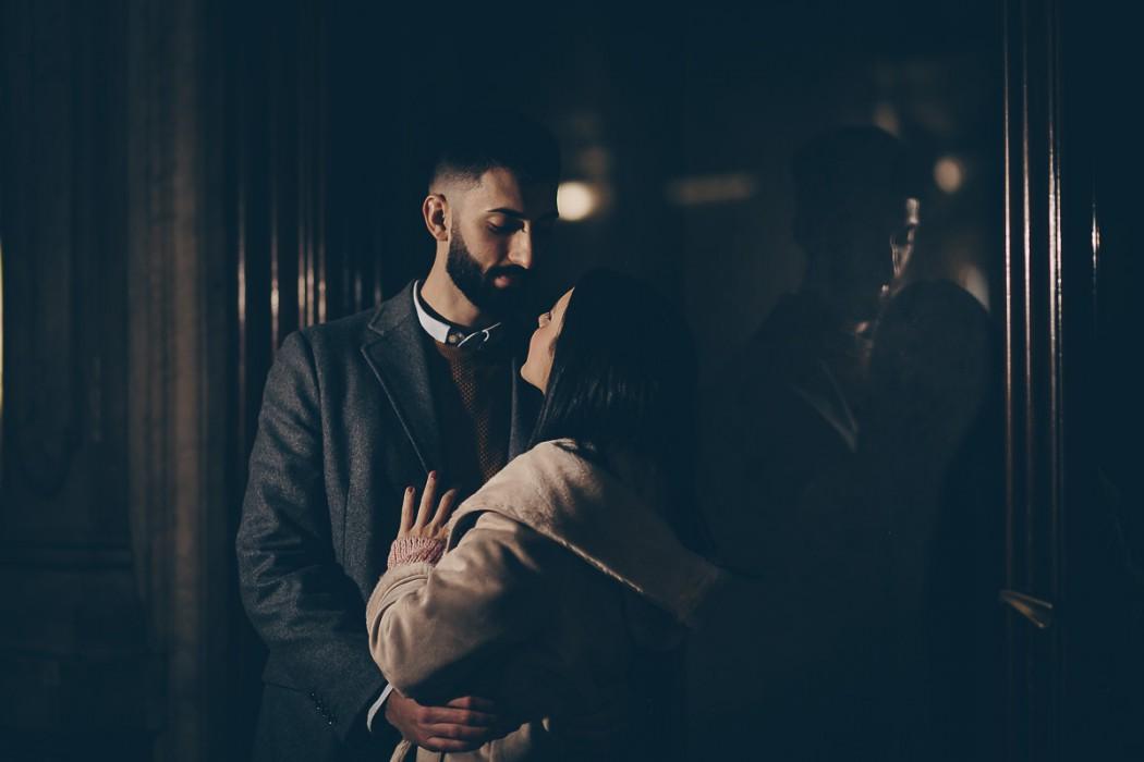 Christmas engagement session a Torino nell'androne di un palazzo di piazza Carignano. I fidanzati si baciano. Flash esterno Godox v1 di lato alla coppia
