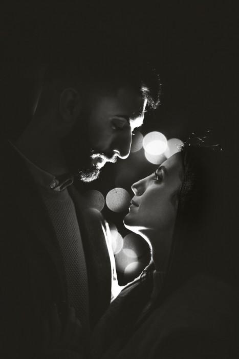 Christmas engagement session a Torino nell'androne di un palazzo di piazza Carignano. I fidanzati si baciano. Flash esterno Godox v1 dietro la coppia. Bokeh. Bianco e nero