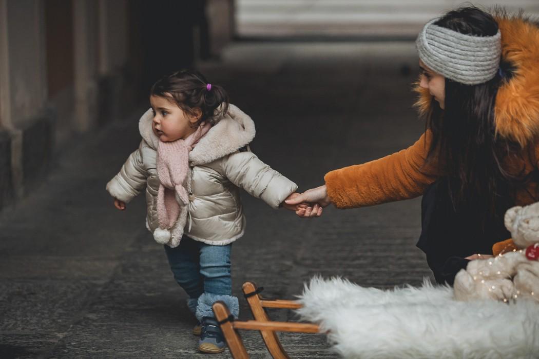 Sessione fotografica di famiglia natalizia a Chieri. Mamma papà e bambina con una vecchia slitta di legno, un orsacchiotto, pacchi regalo e luci di Natale