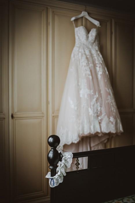 Matrimonio a Crespi d'Adda e alla Tenuta Serradesca. di Maria Acquaroli. Abito in pizzo della sposa di Pronovias appeso all'armadio e giarrettiera