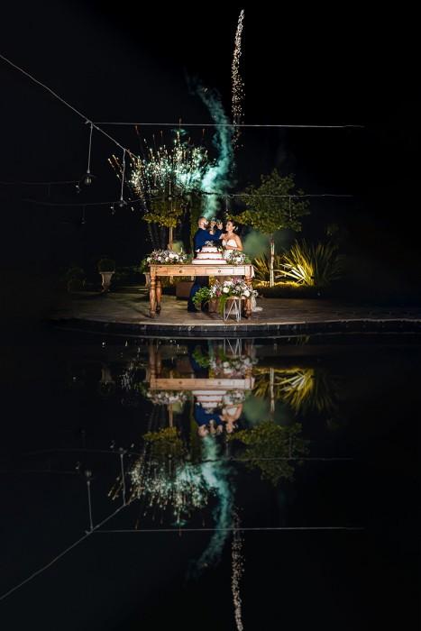 Matrimonio alla Tenuta Serradesca di Maria Acquaroli di Scanzorosciate (BG) Ricevimento. Taglio della torta a bordo piscina con i fuochi d'artificio. Riflesso in piscina