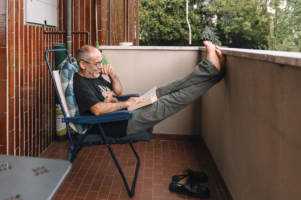 Matrimonio a Crespi d'Adda e alla Tenuta Serradesca. di Maria Acquaroli. Durante la preparazione della sposa, padre che si rilassa sul balcone, leggendo un libro.
