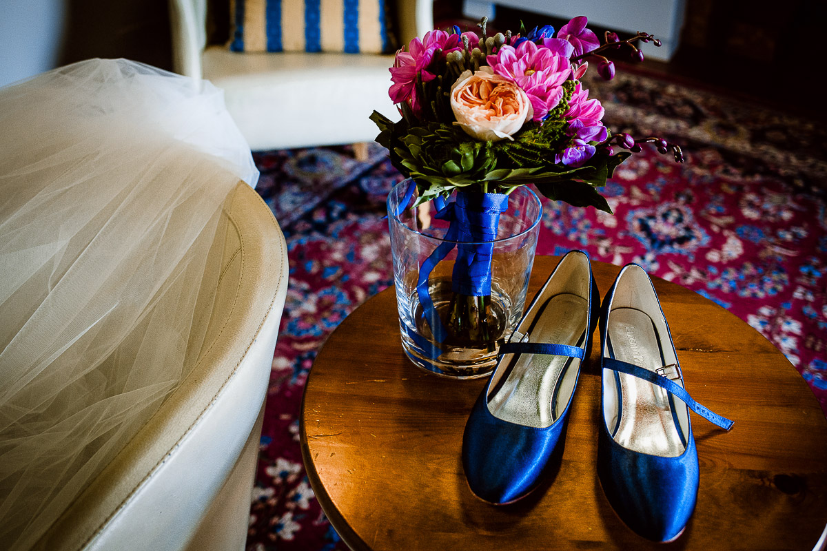 Destination wedding nelle Langhe di Sara e Gabriel. Preparazione della sposa scarpe blu e bouquet